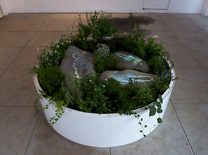 "Mirjana Vodopija, Flower pot 3, 2015/ stones/ pot with soil and plants, Ø 150 cm x 40 cm// video projection on stones 3'08"" loop"